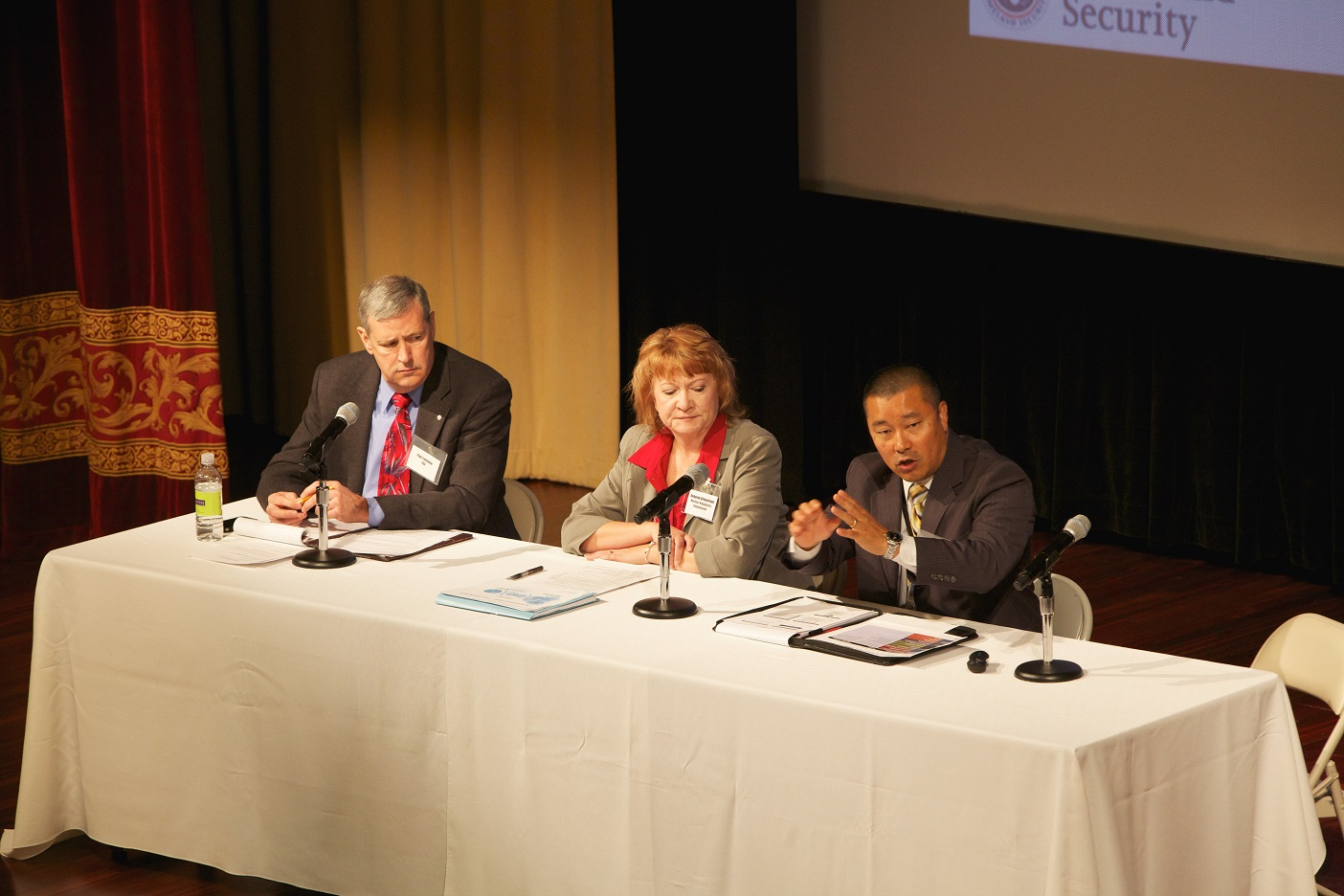Paul Fontaine, FAA, Deborah Armentrout, NRC, and Mark Peasley (speaking), DHS