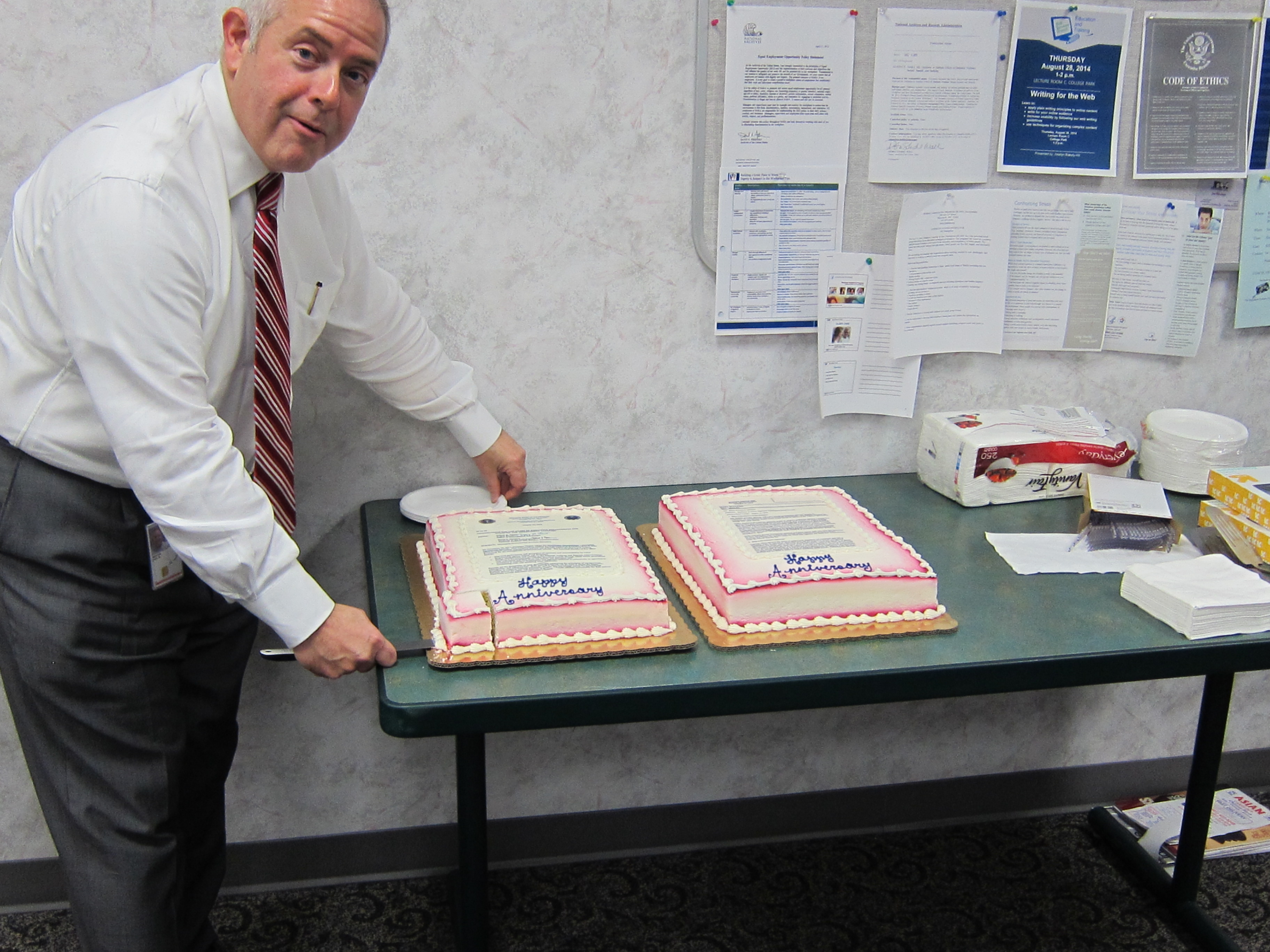 Chief Records Officer for the US Government Paul Wester cutting into the cakes